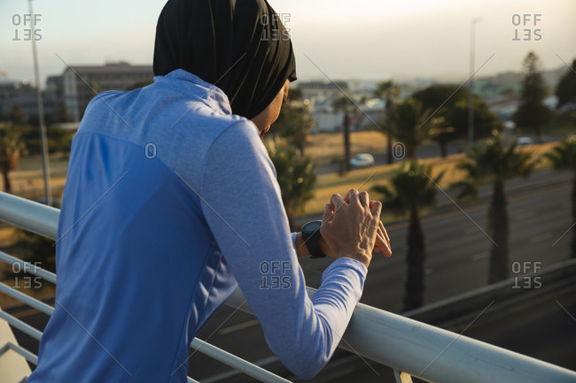 Rear view of fit mixed race woman wearing hijab and sportswear exercising outdoors in the city on a sunny day, checking her smartwatch on a footbridge. Urban lifestyle exercise.