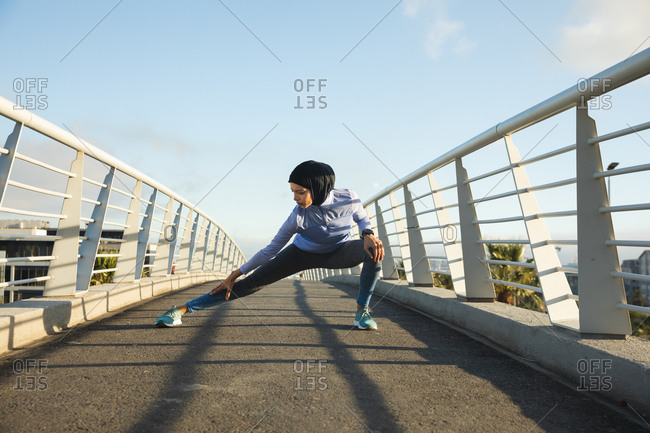 Fit mixed race woman wearing hijab and sportswear exercising outdoors in the city on a sunny day, stretching her legs on a footbridge. Urban lifestyle exercise.