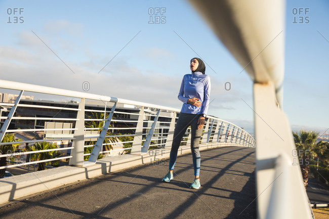 Fit mixed race woman wearing hijab and sportswear exercising outdoors in the city on a sunny day, breathing with hand on her stomach taking break in workout on a footbridge. Urban lifestyle exercise.