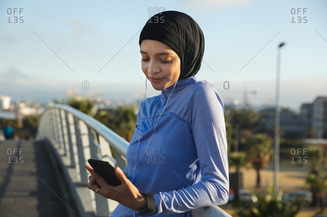 Fit mixed race woman wearing hijab and sportswear exercising outdoors in the city on a sunny day, taking break during workout using smartphone and earphones on a footbridge. Urban lifestyle exercise.
