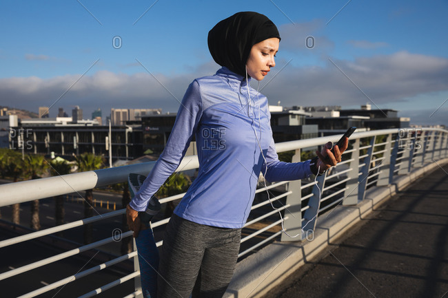 Fit mixed race woman wearing hijab and sportswear exercising outdoors in the city on a sunny day, stretching during workout using smartphone and earphones on a footbridge. Urban lifestyle exercise.