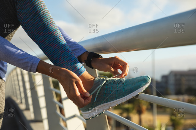 Mid section of fit mixed race woman sportswear exercising outdoors in the city on a sunny day, taking break during workout tying shoelaces on a footbridge. Urban lifestyle exercise.