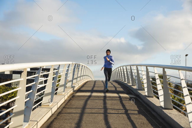 Fit mixed race woman wearing hijab and sportswear exercising outdoors in the city on a sunny day, running on a footbridge. Urban lifestyle exercise.