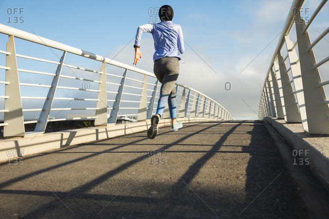 Rear view of fit mixed race woman wearing hijab and sportswear exercising outdoors in the city on a sunny day, running on a footbridge. Urban lifestyle exercise.