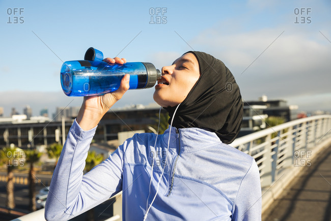 Fit mixed race woman wearing hijab and sportswear exercising outdoors in the city on a sunny day, drinking from water bottle taking break wearing earphones on a footbridge. Urban lifestyle exercise.