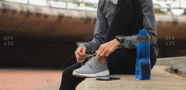 Fit mixed race woman wearing sportswear exercising outdoors in the city, tying shoelaces taking break in urban park, water bottle next to her. Urban lifestyle exercise.