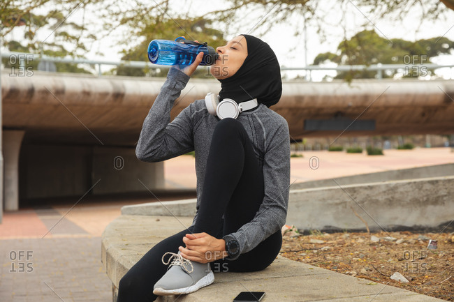Fit mixed race woman wearing hijab and sportswear exercising outdoors in the city, drinking from water bottle taking break wearing headphones on in urban park. Urban lifestyle exercise.