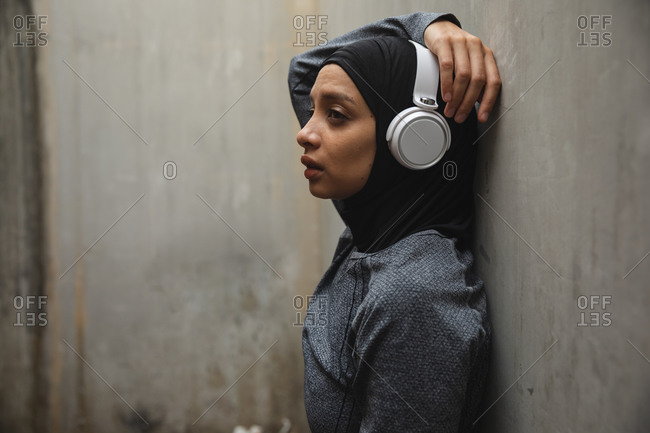 Fit mixed race woman wearing hijab, headphones and sportswear exercising outdoors in the city, leaning against concrete wall. Urban lifestyle exercise.
