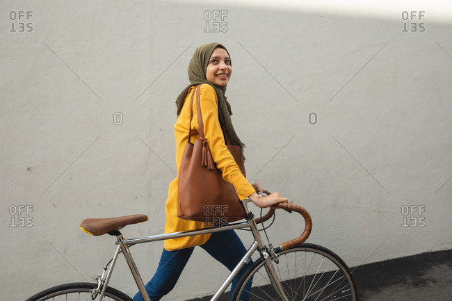 Mixed race woman wearing hijab and yellow jumper out and about in the city, smiling walking with bike. Commuter modern lifestyle.