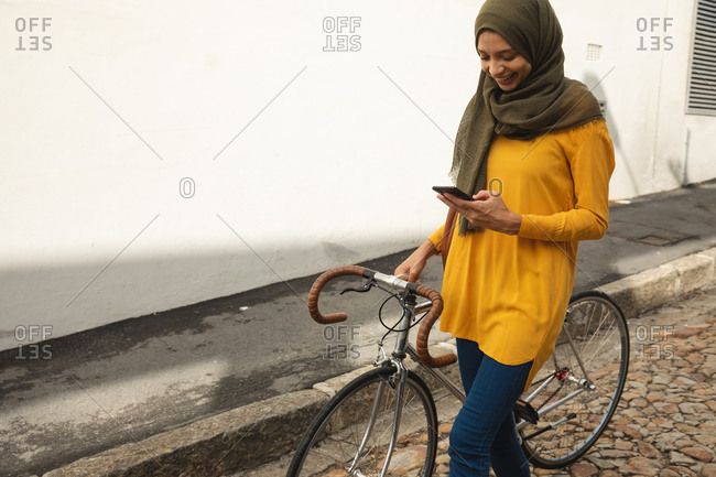 Mixed race woman wearing hijab and yellow jumper out and about in the city, using her smartphone smiling walking with bike. Commuter modern lifestyle.