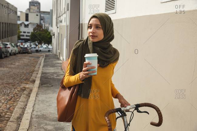 Mixed race woman wearing hijab and yellow jumper out and about in the city, holding takeaway coffee walking with bike. Commuter modern lifestyle.