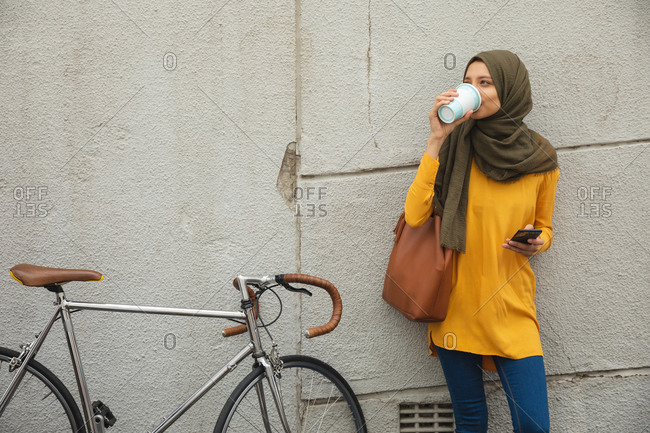 Mixed race woman wearing hijab and yellow jumper out and about in the city, standing by wall drinking takeaway coffee holding smartphone bike next to her. Commuter modern lifestyle.