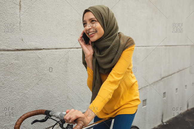 Mixed race woman wearing hijab and yellow jumper out and about in the city, talking on her smartphone smiling sitting on bike. Commuter modern lifestyle.