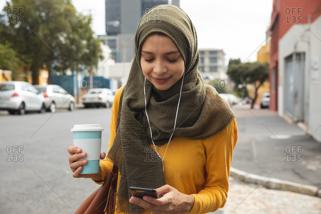 Mixed race woman wearing hijab and yellow jumper out and about in the city, holding takeaway coffee using smartphone with earphones on. Commuter modern lifestyle.