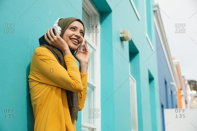 Mixed race woman wearing hijab and yellow jumper out and about in the city, smiling with wireless headphones on leaning against blue wall. Commuter modern lifestyle.