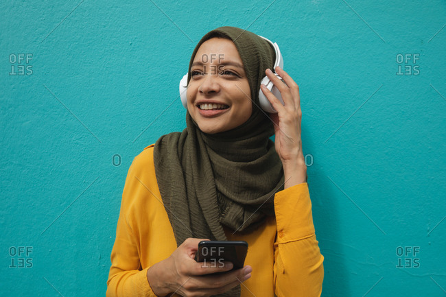 Mixed race woman wearing hijab and yellow jumper out and about in the city, smiling holding smartphone with wireless headphones on. Commuter modern lifestyle.