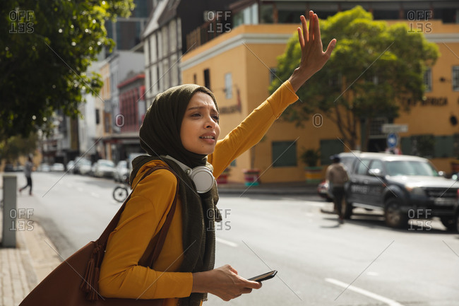 Mixed race woman wearing hijab and yellow jumper out and about in the city, stopping taxi with arm in the air holding smartphone wearing wireless headphones. Commuter modern lifestyle.