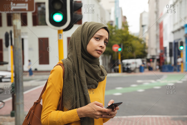 Mixed race woman wearing hijab and yellow jumper out and about in the city, holding her smartphone. Commuter modern lifestyle.