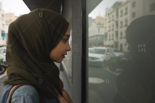 Mixed race woman wearing hijab out and about in the city, standing in the street looking in the shop window. Commuter modern lifestyle.
