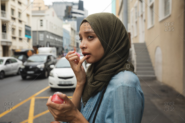 Mixed race woman wearing hijab out and about in the city, standing in street applying lip balm with road traffic behind her. Commuter modern lifestyle.