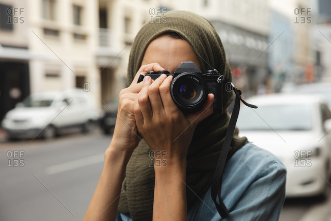 Mixed race woman wearing hijab sightseeing out and about in the city, smiling holding digital camera taking photos. Tourism sightseeing modern lifestyle.