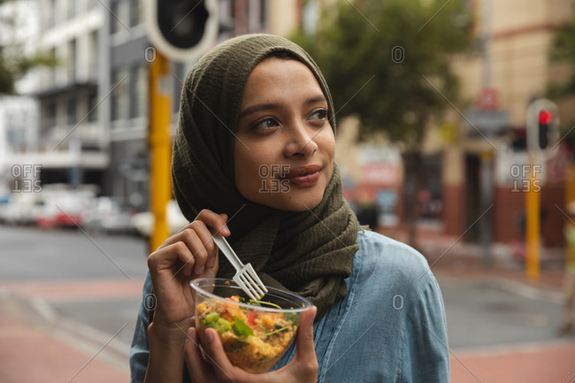 Mixed race woman wearing hijab out and about in the city, standing in street eating takeaway lunch holding bowl and fork, smiling. Commuter modern lifestyle.