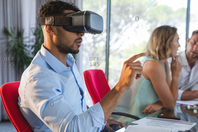 Mixed race businessman sitting at desk using VR headset and virtual 3d interface, with two colleagues discussing in the background. Creative business professionals working in a busy modern office.