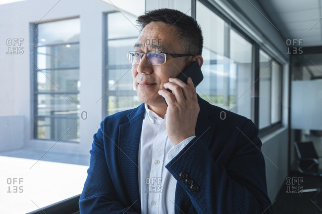 Smart casually dressed Asian male business creative wearing glasses looking out of window smiling, talking on smartphone. Creative business professional working in a modern office.