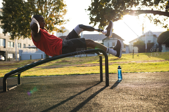 Disabled mixed race man with a prosthetic leg wearing sportswear, working out in a park, doing crunches on bench. Fitness disability healthy lifestyle.