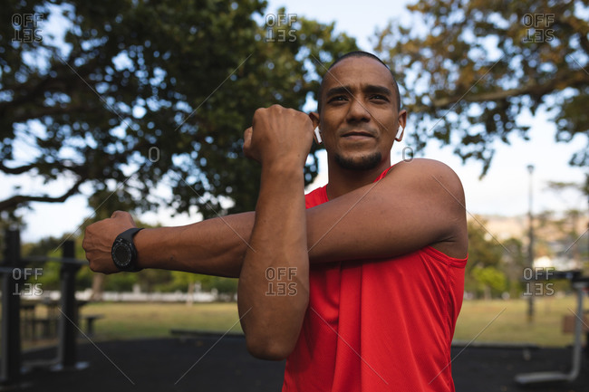 Confident mixed race man wearing sportswear, working out in a park, stretching his arms wearing smartwatch and wireless earphones. Fitness strength healthy lifestyle.
