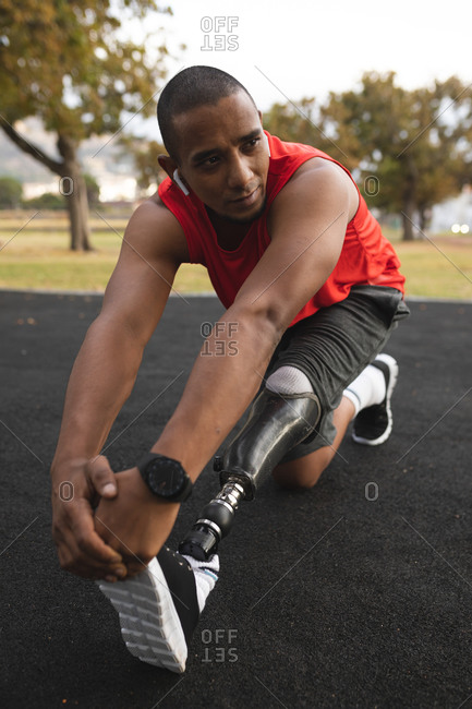 Disabled mixed race man with a prosthetic leg, working out in a park, listening to music on wireless earphones, stretching his legs. Fitness disability healthy lifestyle.