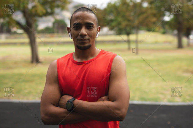 Portrait of confident mixed race man wearing sportswear, working out in a park, looking at camera wearing smartwatch and wireless earphones. Fitness healthy lifestyle.