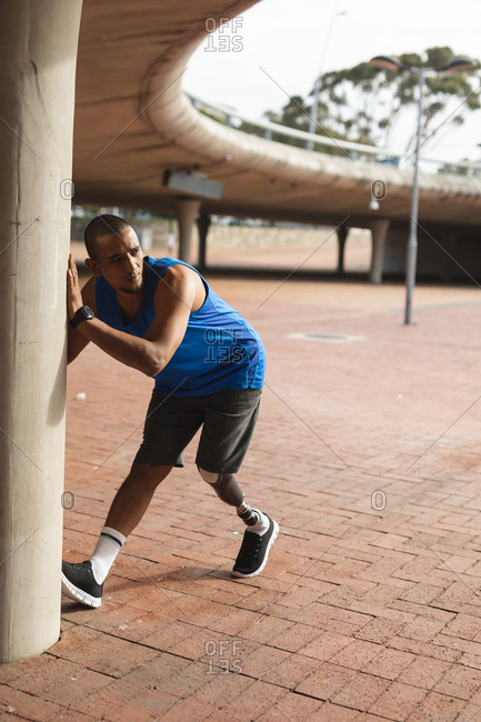 Disabled mixed race man with a prosthetic leg, working out in an urban park, leaning against wall, stretching his leg. Fitness disability healthy lifestyle.