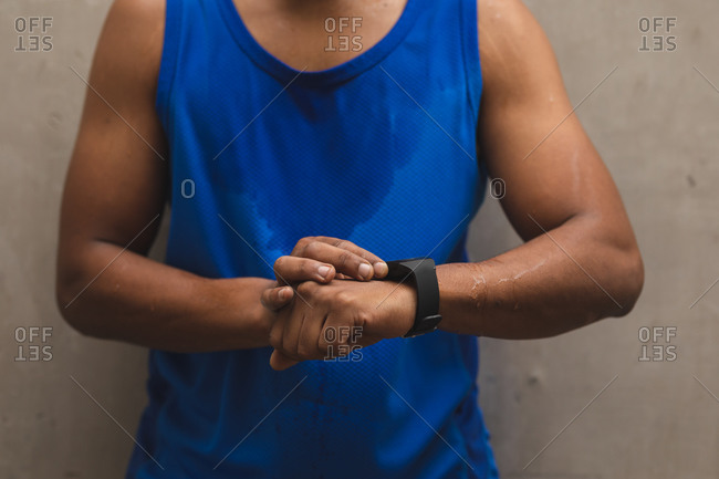 Mid section of mixed race man working out in an urban park, wearing sportswear taking a break checking smartwatch. Fitness strength healthy lifestyle.