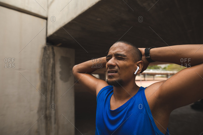 Mixed race man working out in an urban park, wearing sportswear, smartwatch and wireless earphones, wincing with pain and stretching. Fitness strength healthy lifestyle.
