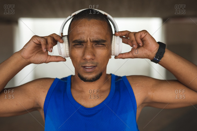 Portrait of mixed race man working out in an urban park, wearing sportswear, smartwatch and wireless headphones, taking a break. Fitness strength healthy lifestyle.