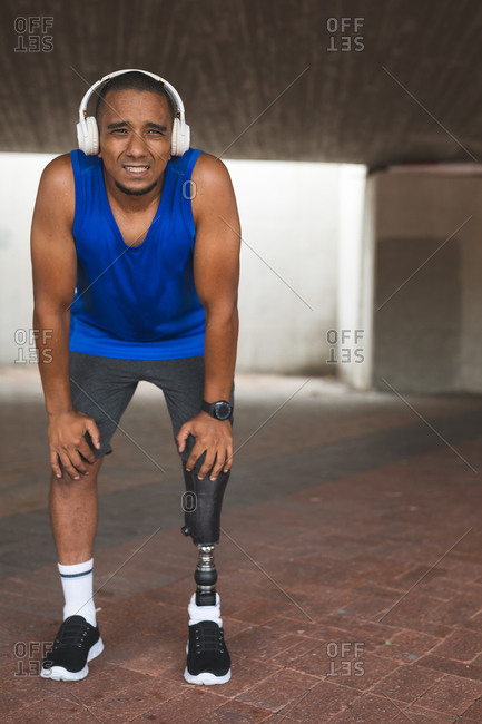 Disabled mixed race man with a prosthetic leg, working out in an urban park, wearing wireless headphones taking a break. Fitness disability healthy lifestyle.
