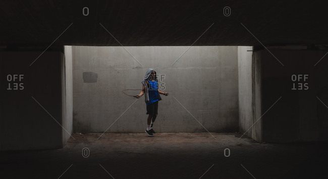 Disabled mixed race man with a prosthetic leg, working out in an urban park, wearing hooded top, skipping with skipping rope. Fitness disability healthy lifestyle.