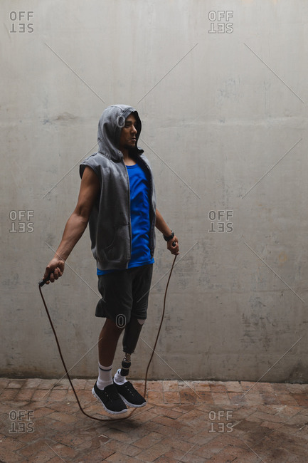 Disabled mixed race man with a prosthetic leg, working out in an urban park, wearing hooded top skipping with skipping rope. Fitness disability healthy lifestyle.