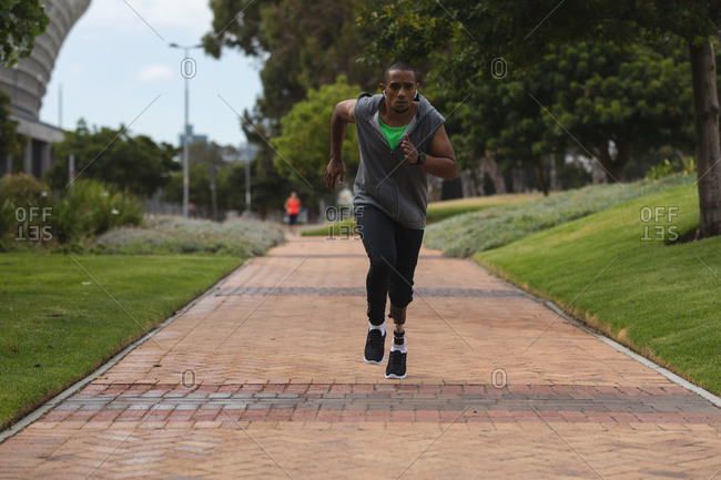 Disabled mixed race man with a prosthetic leg, working out in an urban park, wearing hooded top running on a path. Fitness disability healthy lifestyle.
