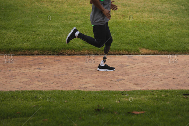 Low section of disabled mixed race man with a prosthetic leg, working out in an urban park, wearing sportswear running on a path. Fitness disability healthy lifestyle.