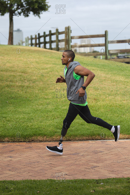 Disabled mixed race man with a prosthetic leg, working out in an urban park, wearing hooded top, running on a path. Fitness disability healthy lifestyle.