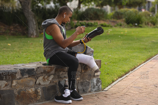 Disabled mixed race man with a prosthetic leg, working out in an urban park, sitting on a wall by a path making adjustments to his prosthetic leg. Fitness disability healthy lifestyle.