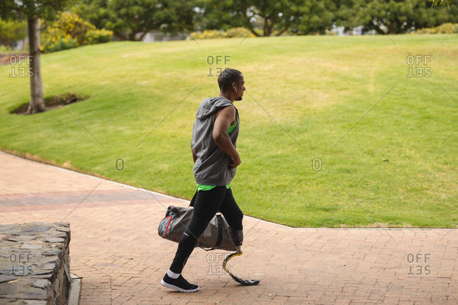Disabled mixed race man with a prosthetic leg working out in an urban park, wearing a running blade, carrying a bag and walking on a path. Fitness disability healthy lifestyle.