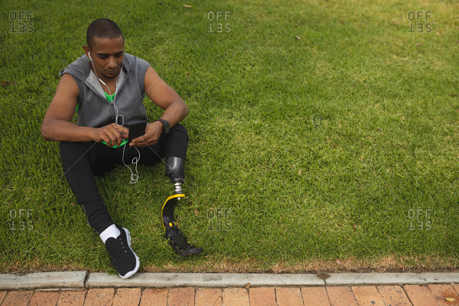 Disabled mixed race man with a prosthetic leg and running blade working out in a park, taking a break, sitting on grass using smartphone and wearing earphones. Fitness disability healthy lifestyle.