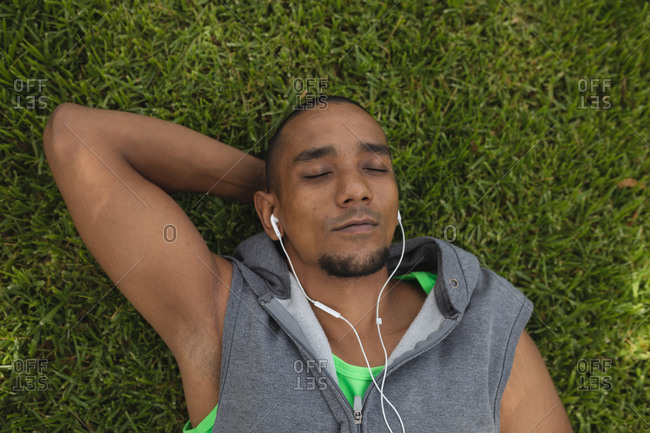 Mixed race man wearing sportswear, working out in a park, taking a break lying on the grass with eyes closed wearing earphones and listening to music. Fitness healthy lifestyle.