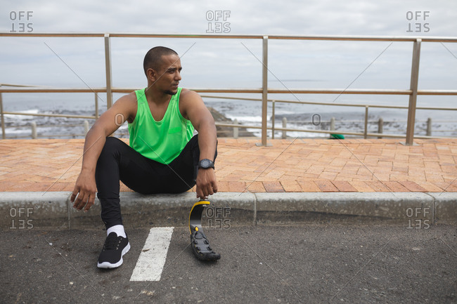 Disabled mixed race man with a prosthetic leg and running blade working out by the coast, sitting on the pavement by a road and taking a break. Fitness disability healthy lifestyle.