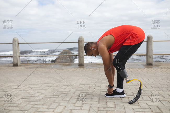 Disabled mixed race man with a prosthetic leg and running blade working out by the coast wearing wireless earphones, bending down to tie his shoelace. Fitness disability healthy lifestyle.