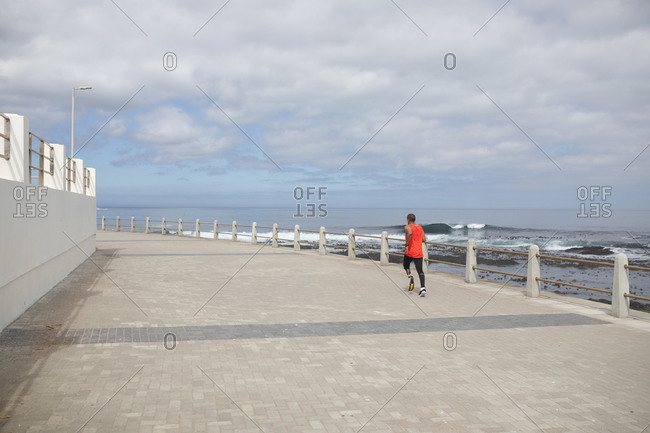 Disabled mixed race man with a prosthetic leg and running blade working out by the coast running on a promenade by the sea. Fitness disability healthy lifestyle.