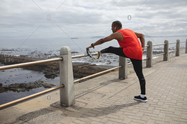 Disabled mixed race man with a prosthetic leg and running blade working out by the coast wearing wireless earphones, stretching legs with his blade on a fence. Fitness disability healthy lifestyle.